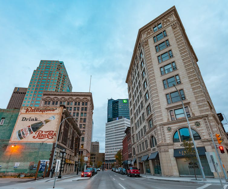 Photograph of downtown Winnipeg with a vintage advertisement on the side of a building.