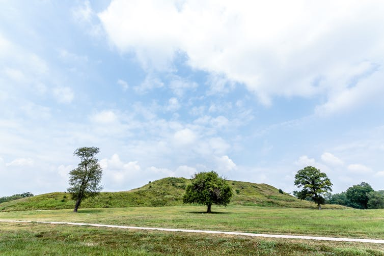 sideview of grass-covered Monks Mound on a sunny day