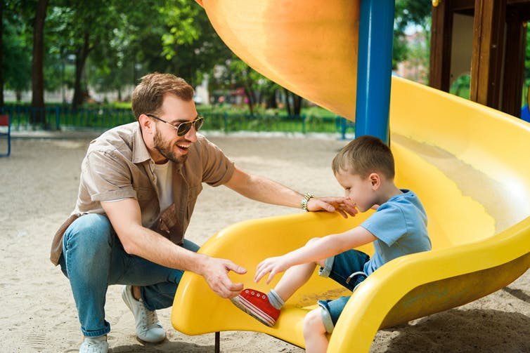A man meets his son at the end of a slide.