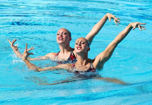 A photograph of two swimmers performing a synchronized routine