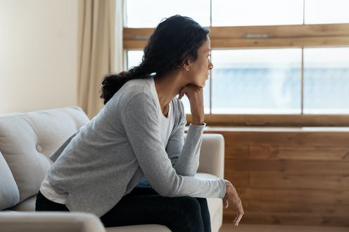 Woman staring out the window looking sad