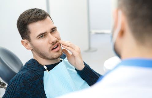 Young man sitting in dentist chair with toothache