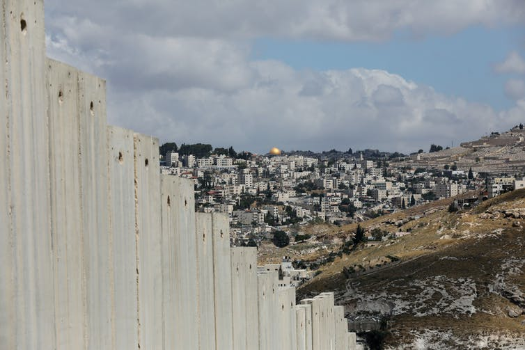 Large wall with Jerusalem in the background.