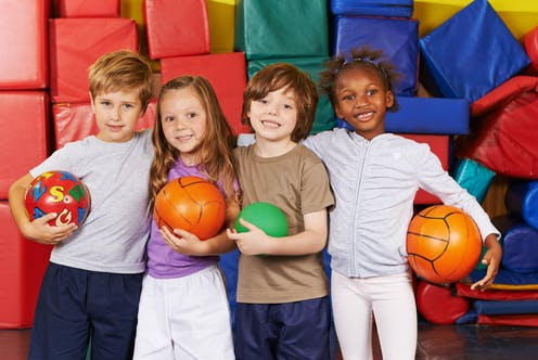 Children together in sports hall with balls