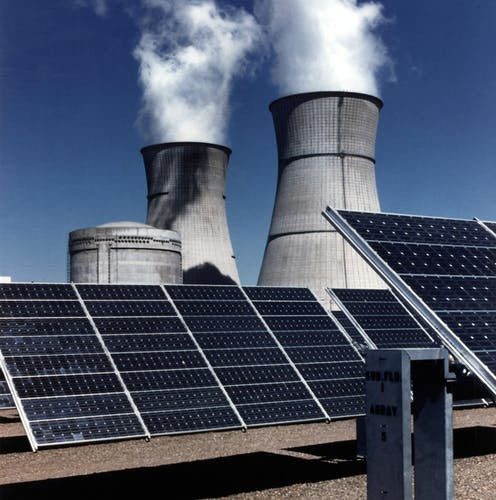Nuclear power plant cooling towers loom over solar panels.