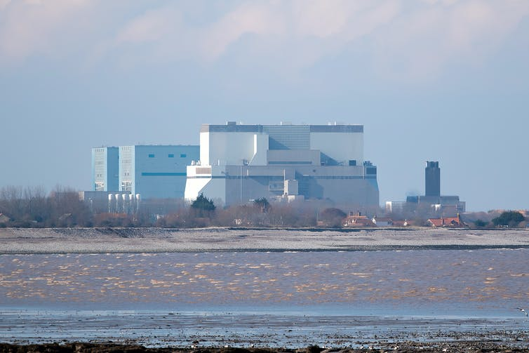 Hinkley Point C power station (a squat building) overlooks a mudflat.