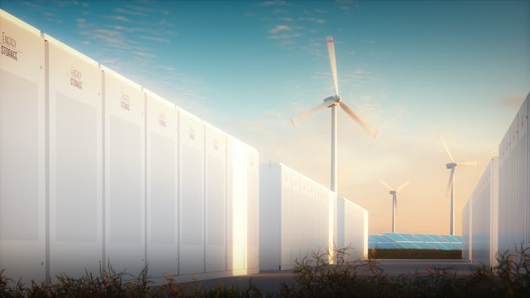 A wall of large, white batteries with wind turbines and solar panels in the background.