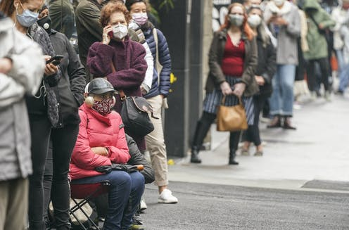 People wearing masks and one sitting in a folding chair wait in a long lineup along a city street.