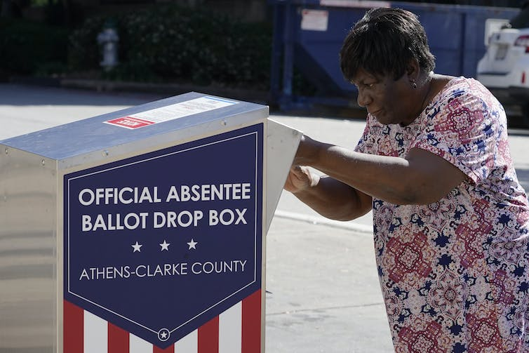 A woman in a flowered shirt puts her ballot into a ballot box outdoors.