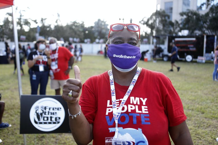 A woman wears a mask and a Let My People Vote T-shirt.