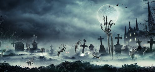 A skeletal hand reaching out of the ground in a spooky graveyard.