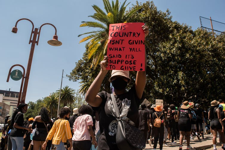 A woman dressed in black and wearing a face mask holds up a red poster that reads, 'This country isn't given what y'all said it's suppose to give.'