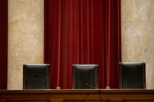 Three judges' chairs in a courtroom