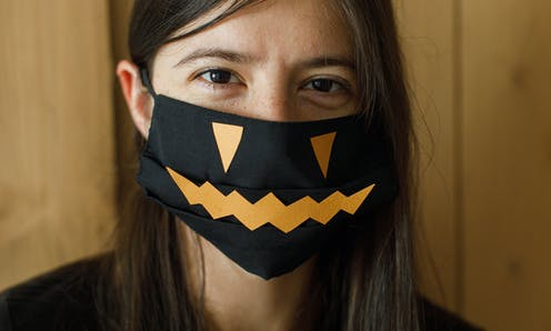 Woman wearing a mask decorated with a pumpkin face