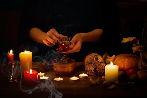 A manicured hand holding a potion amid smoke and candles