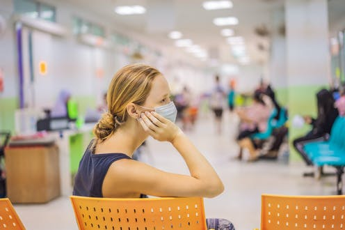 A woman waits in a hospital waiting area.