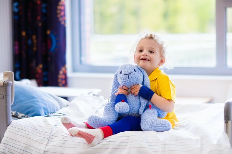 Young happy child sits on hospital bed holding a blue bunny toy.