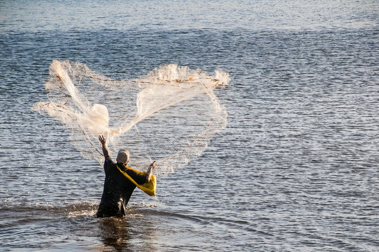 A man using a cast net to fish in the sea.