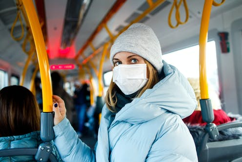 Woman wearing face mask, coat and hat, standing inside a bus