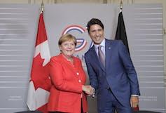 German Chancellor Angela Merkel shakes hands with Prime Minister Justin Trudeau. (AP Photo/Markus Schreiber)