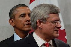 Barack Obama stands behind Stephen Harper.