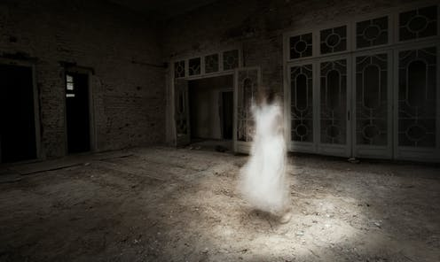 Ghostly image of young woman in white dress appears to float in the middle of an empty room.