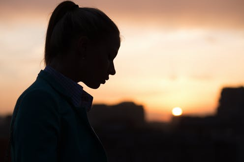 A young woman's silhouette with a blurry urban sunset in the background.