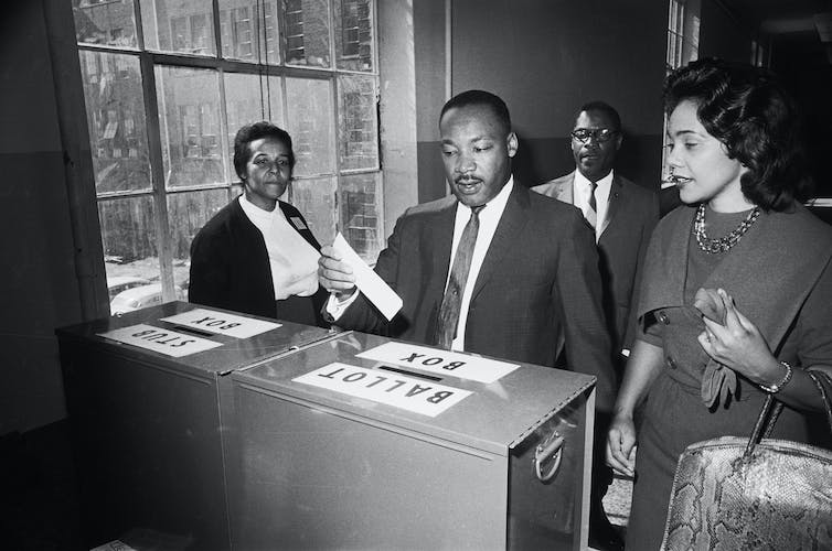 Martin Luther King Jr. votes as his wife, Coretta Scott King, waits her turn.