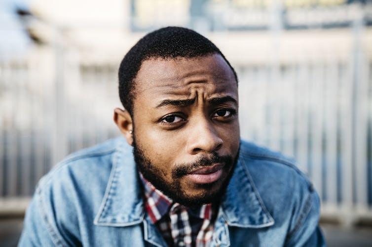 A man in a beard wearing a jean jacket looking quizzical.