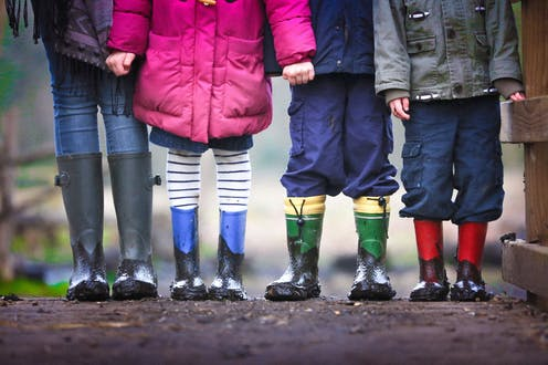 Children in rainboots are seen from the neck down standing in a row.