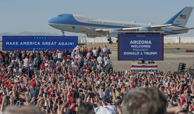 Air Force One aeroplane landing with Trump supporters in front.