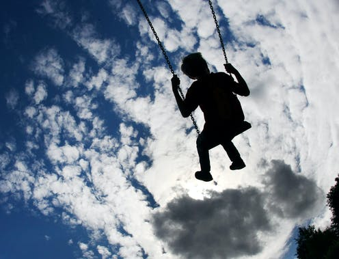 A child seen on swings under a blue sky with clouds on a playground.