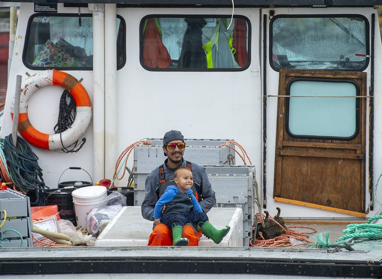 A man sitting at the back of a fishing boat with a smiling toddler on his lap.