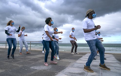 Eight men and women dance on a paved area near the sea, heavy clouds in the background. They are dressed in white T-shirts and jeans and wear matching face masks.