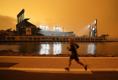 A person is seen running along the McCovey Cove in San Francisco under a burnt orange sky darkened by wildfire smoke.
