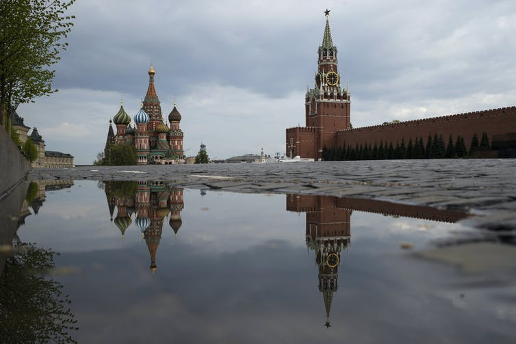 the Kremlin's Spasskaya Tower and St. Basil's Cathedral reflected in rain water puddles in Red Square in Moscow, Russia