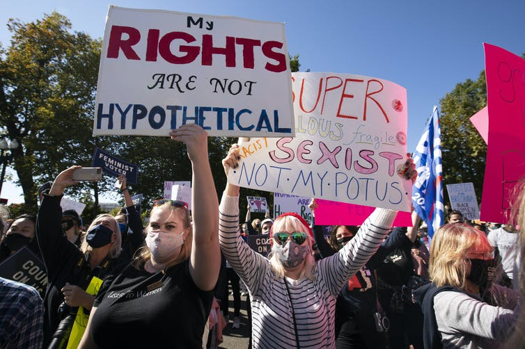 Demonstrators hold placards in front of the Supreme Court during the Women's March in Washington, D.C. The foremost sign reads: My rights are not hypothetical.