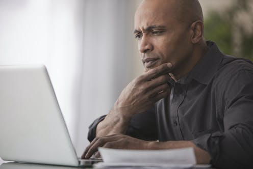 A man with a skeptical expression looks at a laptop