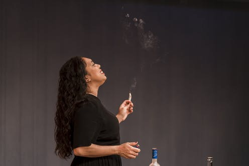 A woman smokes on stage