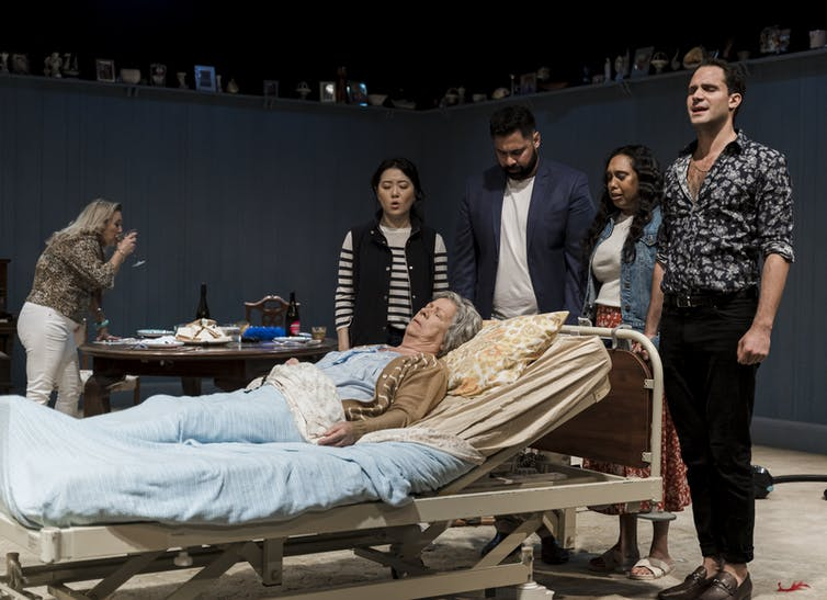 Production photo: the family gather around Nan in a hospital bed