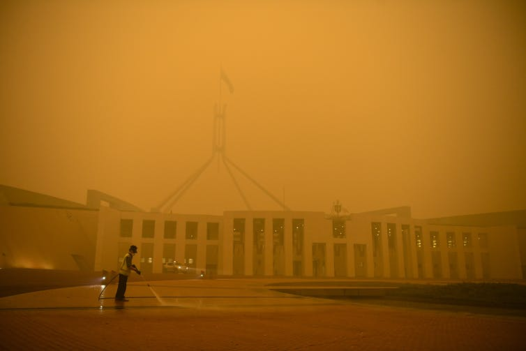 Orange smoke haze shrouds Parliament House.