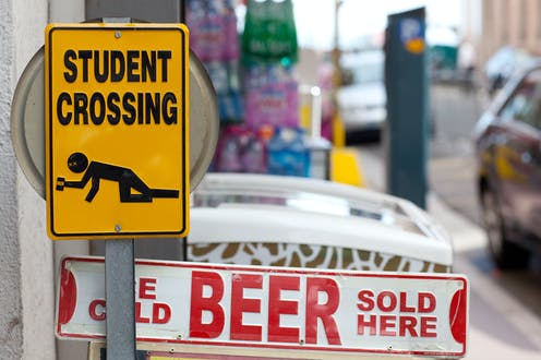 'Student crossing' sign showing person crawling with beer can in hand