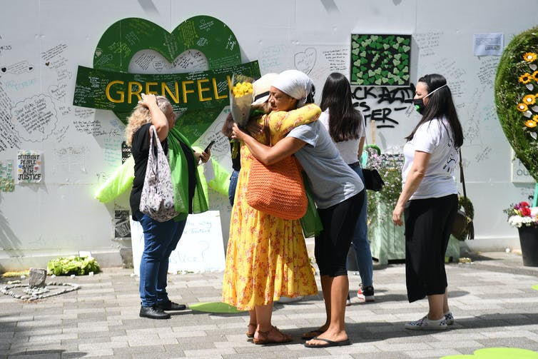 Women hug and look at wall of tributes left for Grenfell victims.