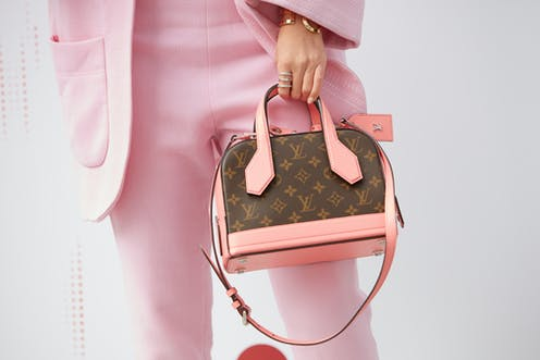 Woman in pink suit modelling a Louis Vuitton bag