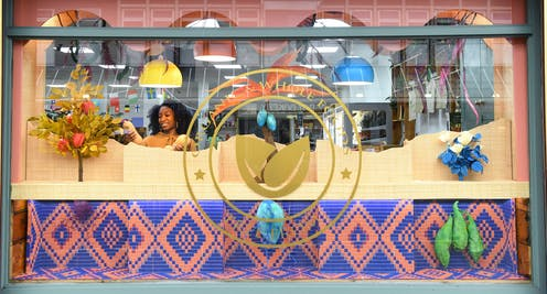 A woman arranges a colourful display in a shop window.