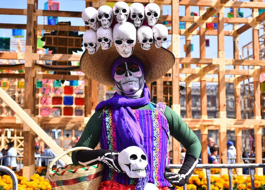 Una mujer con el rostro pintado como un esqueleto participa en las celebraciones del Día de Muertos en la Ciudad de México