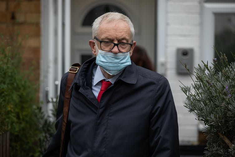 Jeremy Corbyn wearing a covid mask over his mouth.