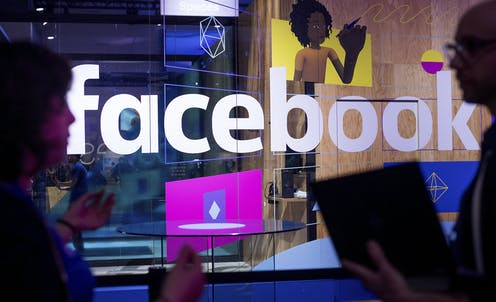 A man and a woman speaking in front of a glass wall containing the Facebook logo