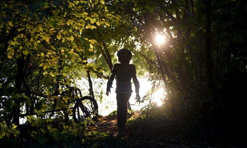 A child walks through a wooded area