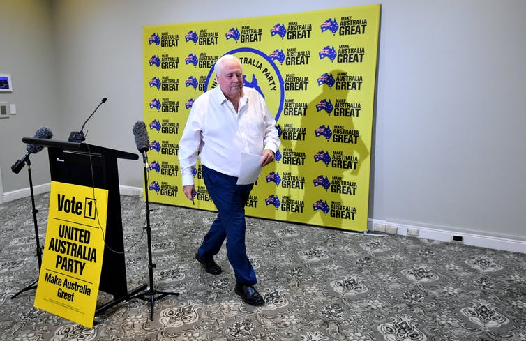 Clive Palmer walks away from a press conference.